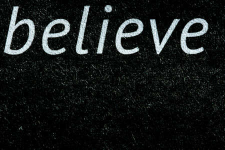 Macro image of the word believe on newsprint in black and white Stock Photo