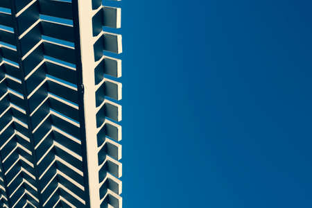 Timber roofline of a cabana against a clear blue sky
