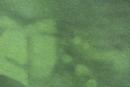 Macro image of green gradient CMYK dots on newsprint