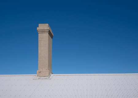 Old chimney on corrugated iron roof against a clear blue sky Stock Photo
