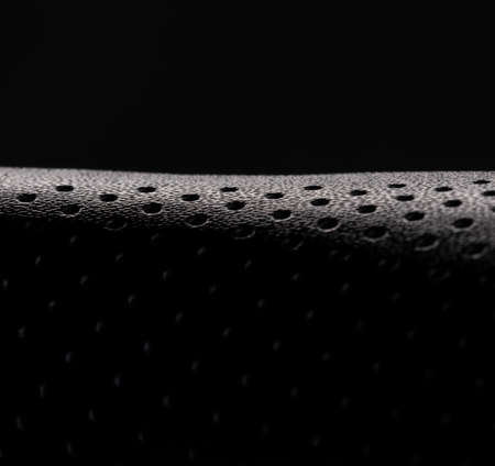 Macro image of the texture of a black bicycle seat against a black background