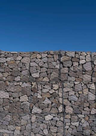 Duży detal ściany gabionowej w słoneczny dzień na tle czystego, błękitnego nieba