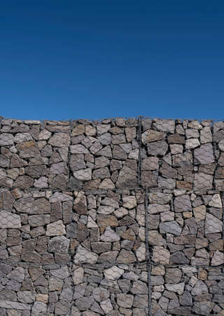 Large gabion wall detail on a sunny day against a clear blue sky