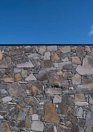 High stone wall in a landscape garden against a clear blue sky