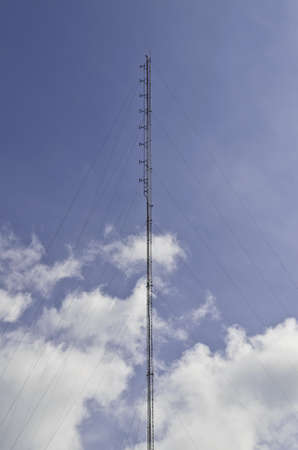 Telecom tower for radio mobile against blue and cloudy sky  photo