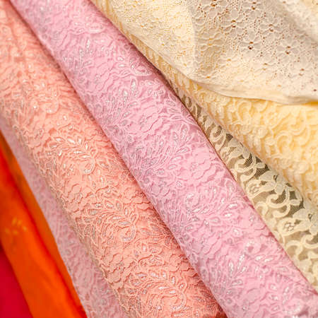 Fabric store with stacks of colorful lace textiles