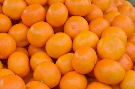 Many fresh mandarin oranges on market