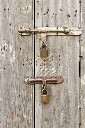 Old wooden doors are locked with padlocks  photo