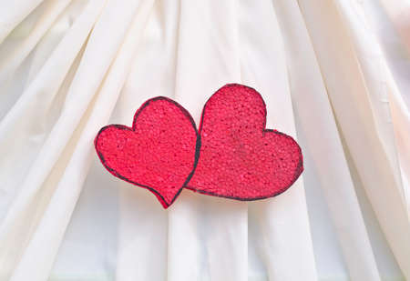 synthetically: red foam board heart shape decorated on beige cloth Stock Photo