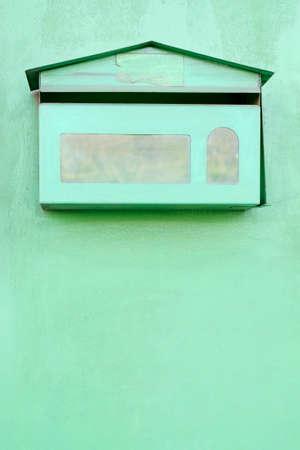 Green post box on green wall