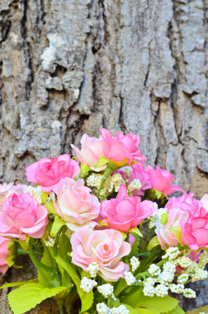 Pink artificial rose bouquet with tree trunk background Stock Photo