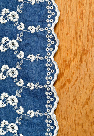 jeans fabric with white flower embroidery laid over plywood bacckground
