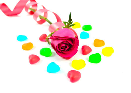 red rose with colorful heart shape jelly candy on white background- valentines concept Stock Photo