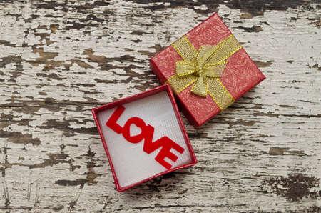 Love alphabet in gift box on grunge wood background photo