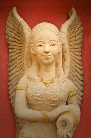 sexy angel: stone woman angel statue against orange background