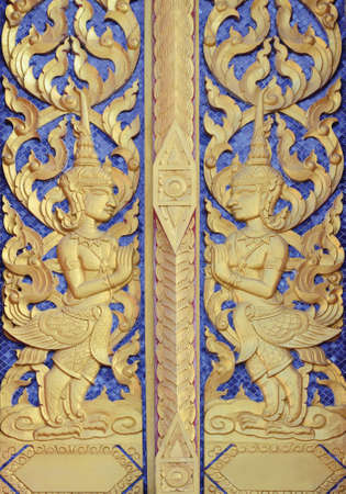 woodcraft: Thai temple door golden angle sculpture at public temple in Pattalung province
