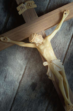 golgotha: A carved statue of the Crucifixion of Jesus Christ on wood background in vintage style