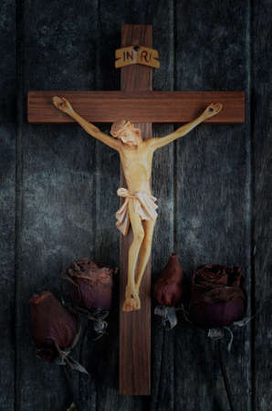 trustworthiness: A carved statue of the Crucifixion of Jesus Christ with dried roses on wood background Stock Photo