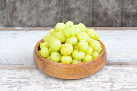 Star gooseberry fruit in wood bowl on wooden background