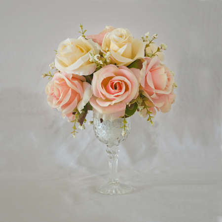 Artificial roses vase flowers on grungy grey background Stock Photo