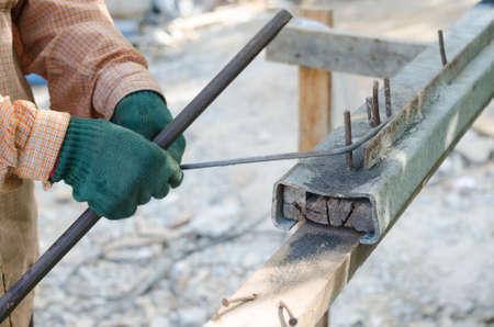 Labor hand bending reinforcement steel at construction site Stock Photo