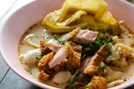 spicy wonton soup with crispy pork in pink bowl