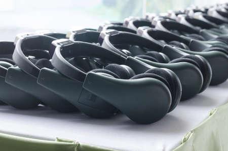 Dark green headphones stack on white table Stock Photo