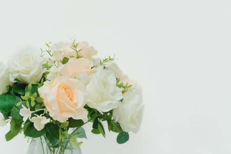 Beautiful artificial roses in arrangement in glass vase  with copy space Banco de Imagens