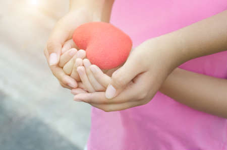 Soft focus of adult and child hands holding heart
