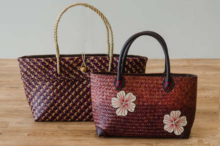 Hand woven Bags  from Krajood, a kind of sea grass on wood background Standard-Bild