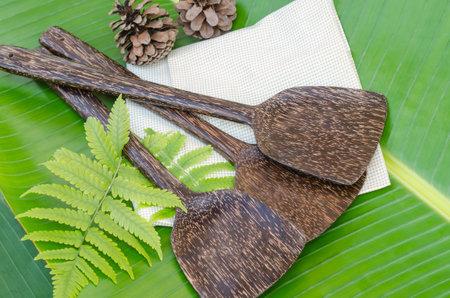 Sugar palm wooden spatulas on green napkin and green banana leaf