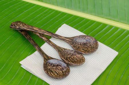 Palm sugar spoons on green banana leaf