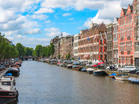 A canal in Amsterdam with small boats docked alongside, traditional Dutch buildings and a tree covered bridge in the distance taken on a blue day with clouds. Editorial