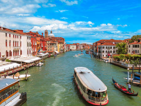 Canal in Venice with water taxi and Venetian buildings along the water on a blue summer day and clouds.