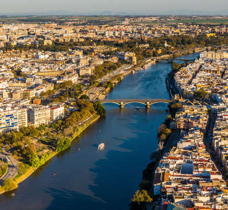 Drone view of old downtown Sevilla at sunset showing Guadalquivir river, Puente de Triana, Plaza de Toros, Plaza de España, Triana, Torre del Oro, Calle Betis, Parks and other historical buildings