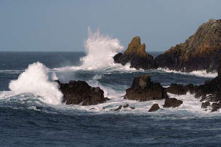 simultaneously: WAVES BREAKING ON ROCKS SIMULTANEOUSLY
