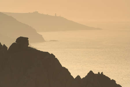cliff edge: COUPLE ON CLIFF EDGE WATCHING THE SUNSET Stock Photo