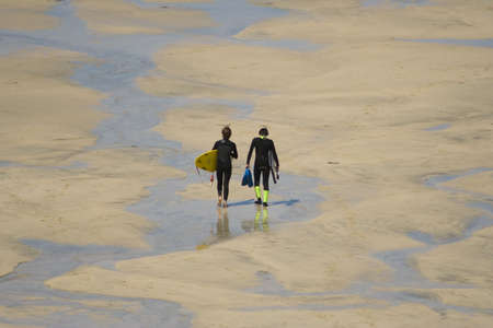 surfers: TWO SURFERS WALKING ON THE BEACH (9621)