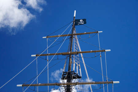 tall ship: TALL SHIP MAST WITH THE PIRATES FLAG FLYING AGAINST THE SKY AND CLOUDS