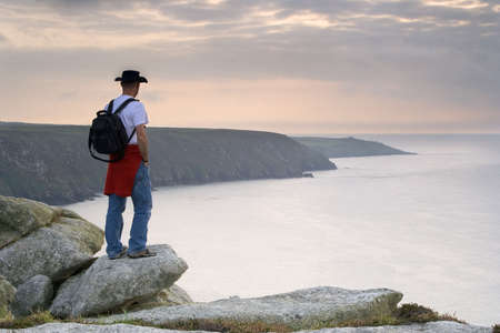 ruck sack: Male trekker standing on top of the Cornish cliffs and looking out to sea into the distance