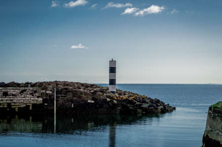 A lonely lighthouse guards the rocky harbor, looking out to sea in Northern Ireland.