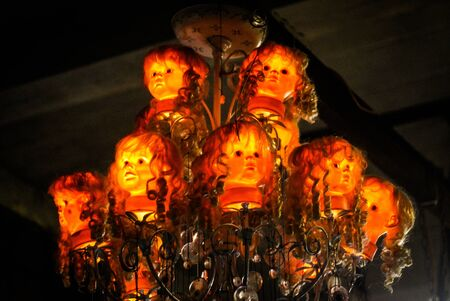 An antique chandelier remade using doll heads Stock Photo