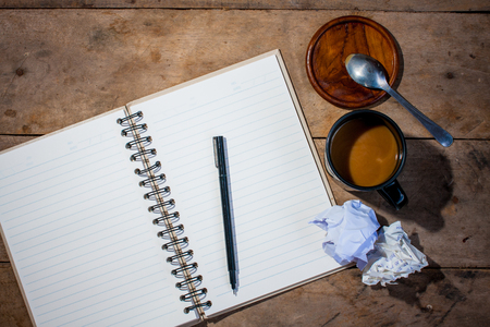 notebook pen  cup of coffeeand crumpled paper in wood table photo
