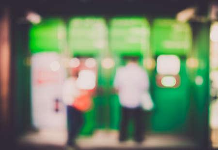 automatic transaction machine: desenfoque de fondo la gente le quita el dinero en el cajero autom�tico (ATM)