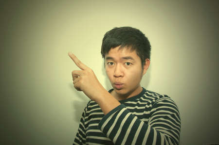 chose: Asian handsome man pointing finger. Face expression gesture body language. Vintage Tone Stock Photo