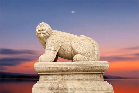 mythological: Haechi,Statue of a mythological lion-like animal with sunset.