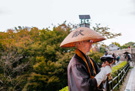 dera: Kiyomizu temple , Kyoto, Kansai district, Japan - NOVEMBER 15, 2015 : Japanese monk praying and asking for donations in front of the majestic Kiyomizu temple in Kyoto, Japan. Kiyomizu temple is one of the most famous temple in Kyoto.