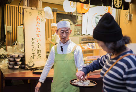 undefined: Kyoto, Japan - December 11 2015: Undefined japanese chef giving some example for tourists in the market around Kiyomizu-dera Temple.