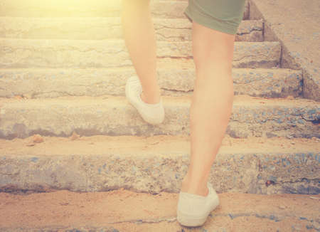 lay forward: Close-up Man with sneaker shoes running on the step. International sun light and vintage tone.