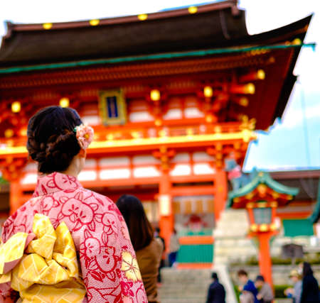 Young girl wearing Japanese kimono standing in front of japanese Temple.